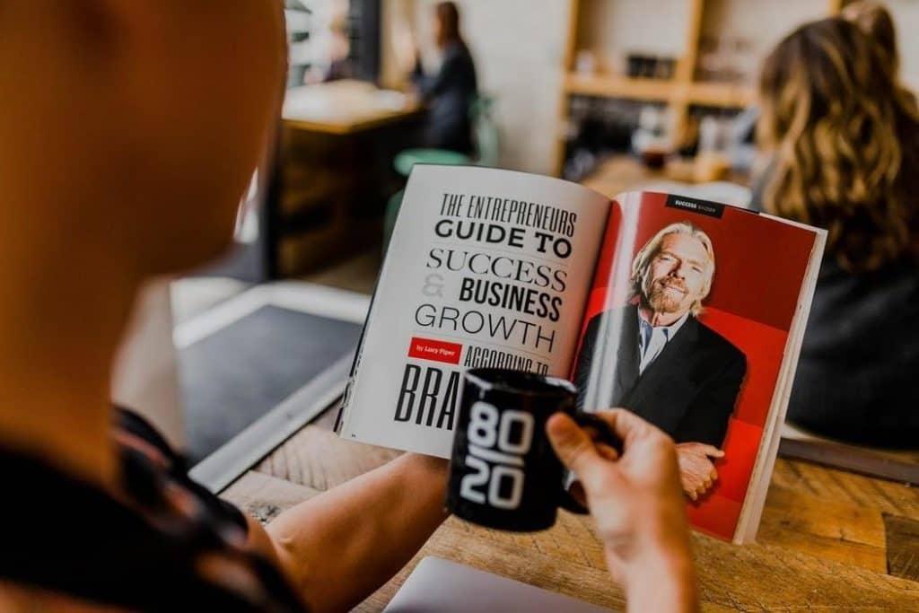 persona che legge un libro sul business mentre bene un caffè