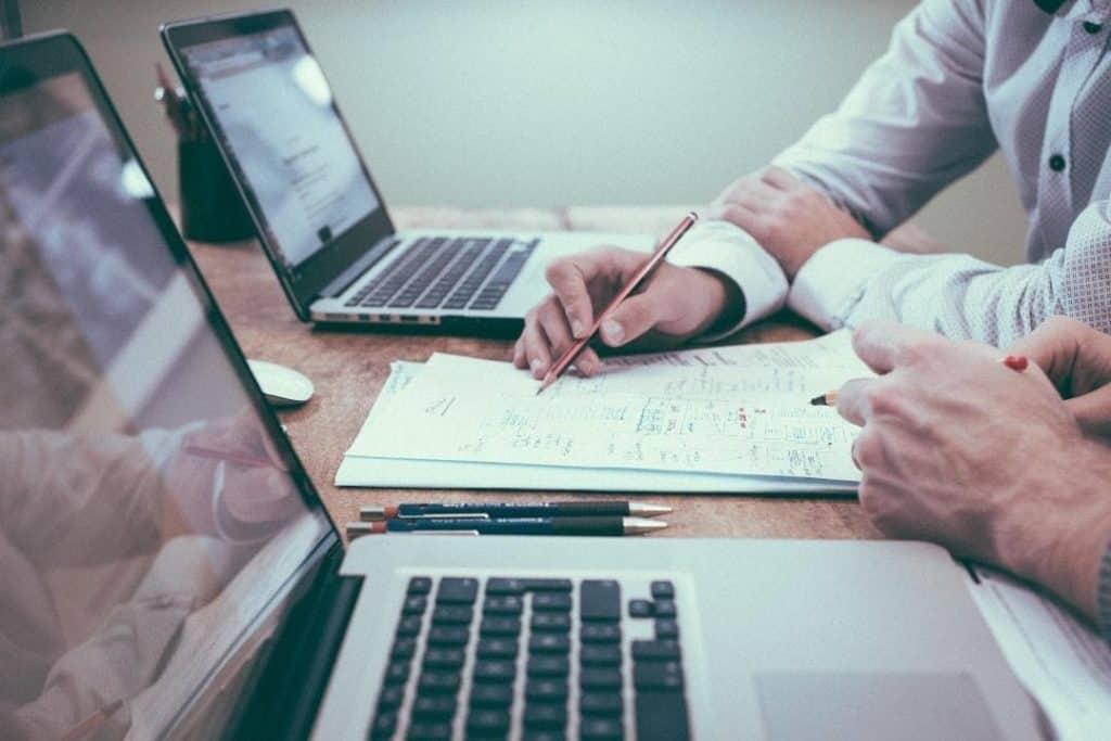Una persona seduta al tavolo che sta prendendo appunti su un foglio mentre usa un computer