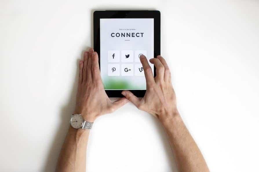 Immagine che raffigura un tablet con i pulsanti dei social ed una persona che sta cliccando su uno di questi
